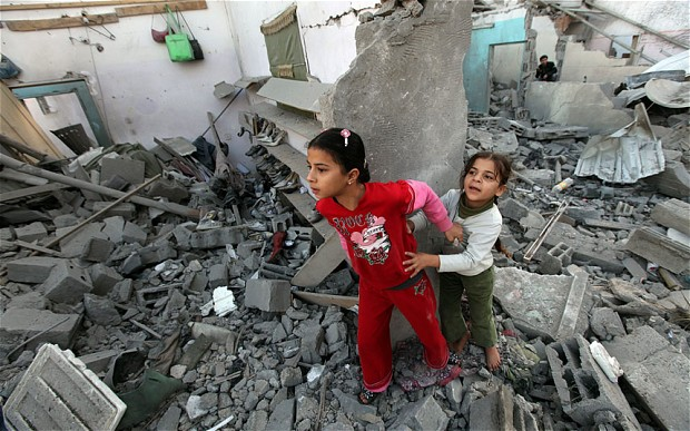 Children in Gaza walk in the rubble.